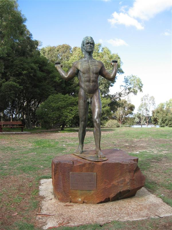 A statue of a man in the middle of the kangaroo colony. I bet the roos mock him because he's pretending to carry something really heavy.