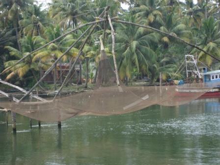Chinesische Fis chernetze. Die findet man in den Backwaters ohne Ende. Über einen Hebel werden die Netze ins Wasser gelassen. In der Mitte befindet sich meist eine Lampe zum Fischschwärme anlocken und schlussendlich werden sie wieder hochgezogen.