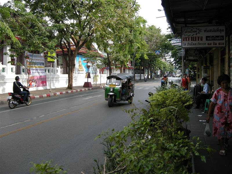 a tuk-tuk zooming down the street