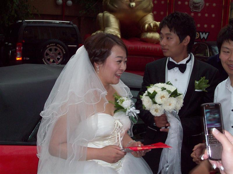 The ayi (groom's mom) gives the bride a red envelope.