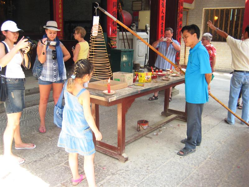 Girl lighting a coil of incense